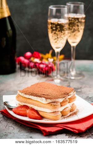 Tiramisu with strawberry and glasses of champagne on the table. Valentines concept.