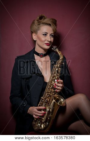 Sexy attractive woman with saxophone posing on red background. Young sensual blonde playing sax. Musical instrument, jazz. Beautiful woman in black posing with saxophone, studio shot