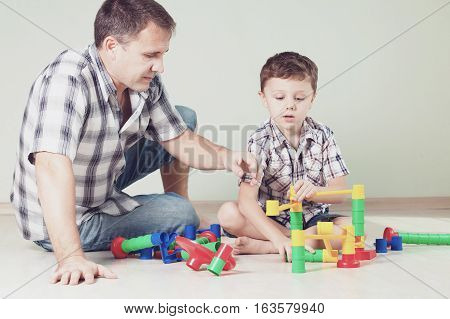 Daddy With Little Boy Playing With Toy On The Floor At The Day Time.