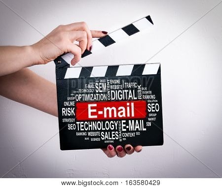 E-mail concept. Female hands holding movie clapper.