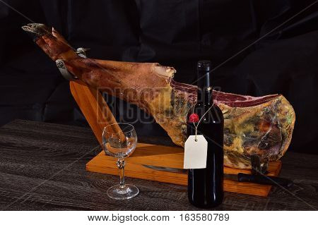 Bodegon with jamon, bottle of red wine and wineglass