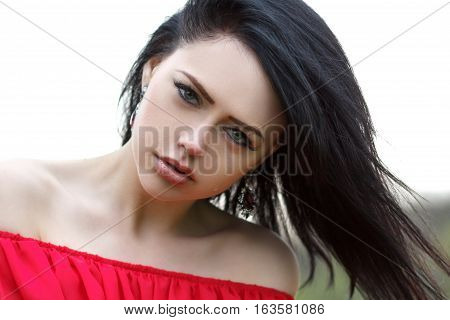Portrait of a beautiful young girl with green eyes and bare shoulders in a red dress on a green background summer nature.