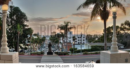 Father statue overlooking Downtown Ventura as dusk glows in sky.