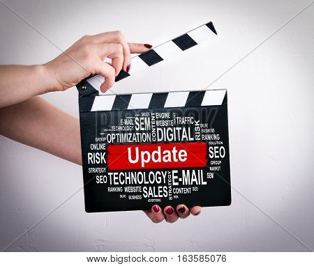 Update concept. Female hands holding movie clapper.
