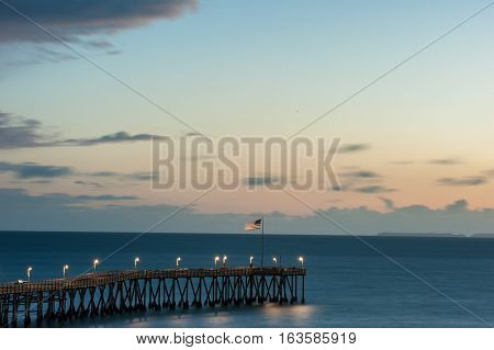 American Flag waving in sea breeze at end of Ventura Pier at dusk.