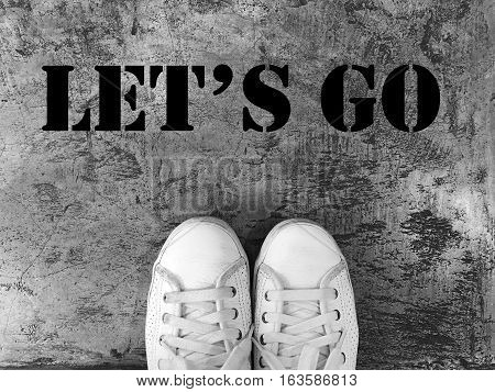 let's go word, white shoes on the concrete texture background