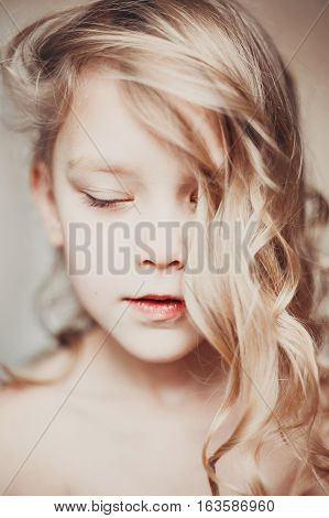 Portrait of a pretty little girl with closed eyes. Age of innocence.