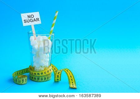 Glass with straw full of sugar cubes with yellow tape. Lot of sugar, cocktail