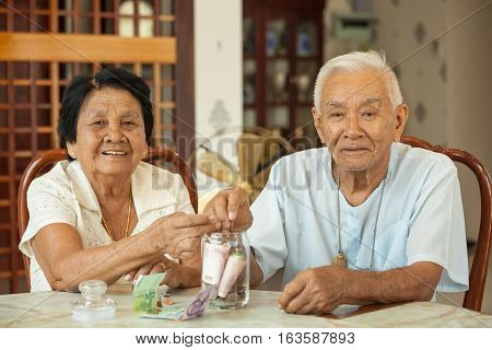 senior couple counting money with glass bank