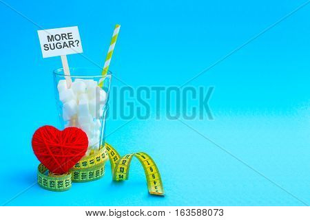 Glass with straw full of sugar cubes with yellow tape and heart. Lot of sugar