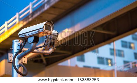 Security camera equipment and traffic concept - Surveillance security camera equipment on pole in evening traffic light and copyspace