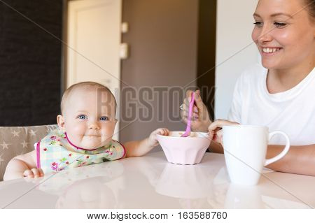 Portrait of a loving mother feeding her happy baby girl. Newborn child fed with by mom.