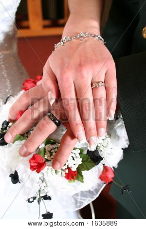 Wedding Couple Holding Hands Showing Rings Over Wedding Flowers