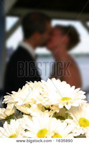 Wedding Couple Kissing Behind Bridal Bouquet, Soft Focus Background
