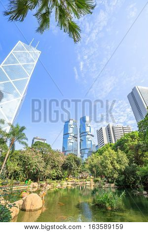 Scenic view of the pond at the lush green garden of Hong Kong Park surrounded by modern skyscrapers in the Central business district in Hong Kong island. Sunny day with blue sky.