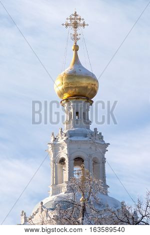 Top of Russian country church with golden cupola in winter closeup