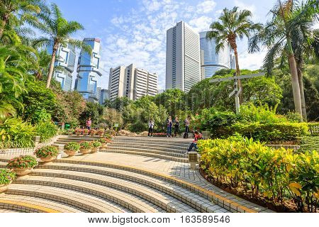 Hong Kong, China - December 7, 2016: asian people sitting on stairs of the famous Hong Kong Park surrounded by Lippo Centre skyscrapers in the Central business district. Sunny day with blue sky.