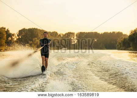 Male Water Skiing Behind A Boat On Lake