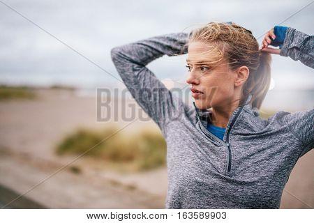 Female Runner Tying Up Hair Before A Run