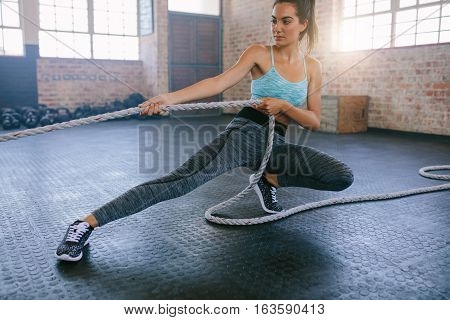 Shot of young woman exercising with rope at a gym. Fitness female pulling rope at gym.