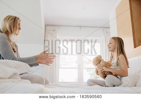 Shot of little girl and woman playing with teddy bear. Mother and daughter playing with teddy bear on bed at home.