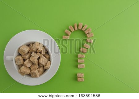 Diet, unhealthy sweet addiction concept. White cup full of brown sugar cubes and question mark of them on greenery background. Top view. Flat lay. Copy space for text