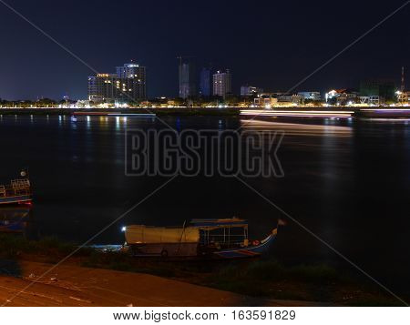 Night city skyline of Phnom Penh with a river in front and a moving boat as light stripes light ray and a boat in the foreground