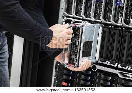 Midsection of IT technician installing blade server in chassis at data center