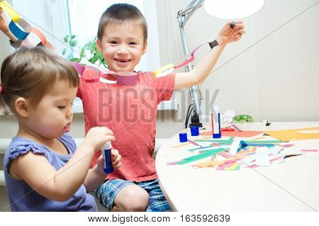 kids development - children making paper colored garland with glue on table siblings craft brother and sister playing together