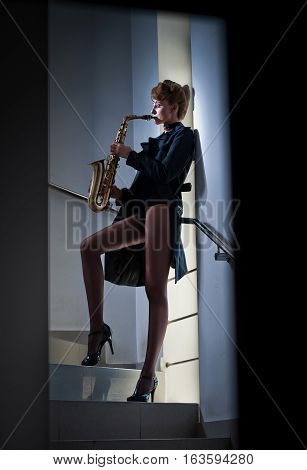 Sexy attractive woman with saxophone and long legs posing on stairs. Young attractive blonde playing sax. Musical instrument. Jazz. Portrait of a sesual female posing with saxophone