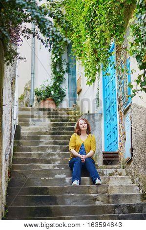 Tourist sitting on stairs in Positano beautiful Mediterranean village on Amalfi Coast (Costiera Amalfitana) in Campania Italy