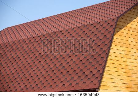 Wooden house wall from timbers and brown soft roof tile over cloudless sky closeup