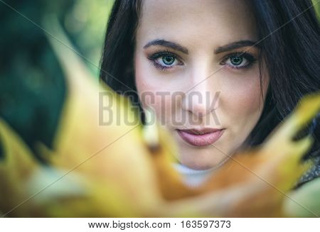 Pretty serene young woman looking over colorful yellow autumn leaves at the camera with a quiet gentle smile close up of her face