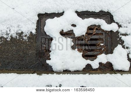 Snow clogged drain with small stream of water
