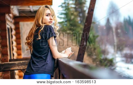 Beautiful Girl Standing On The Porch Of A Wooden House In The Winter Forest And Languid Tenderly Loo