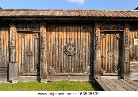 Old wooden gate with woodcarving elements at summer day
