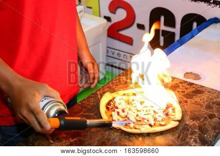 Chef burn fired a mozzarella cheese topping in pizza with small kitchen blow torch