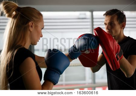 Young competitors trains in boxing in gym
