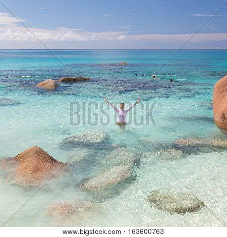 Woman arms rised wearing bikini and lycra top enjoying swimming and snorkeling at amazing Anse Lazio beach on Praslin Island, Seychelles. Summer vacations on picture perfect tropical beach concept.