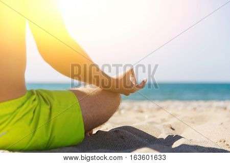 Guy practicing yoga at seaside on sunny day