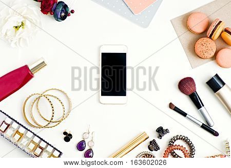 Flat lay for fashion blog and social media. Woman's glamour beauty products and accessories on a white background. Foundation brushes mascara jewelry perfumes flower macarons spiral hair ties and hair clips. Copy space for text