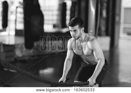 Black and white photo of sports man in gym at punching bag
