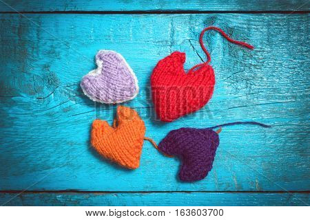 Valentine's Day. Colorful knitted hearts. Red heart on the blue boards. Valentines day. Heart pendant. Red heart. Valentine cards. Space for text. Eighth of March. International Women's Day.