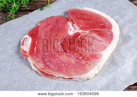 Raw gammon steak on crumpled paper with thyme.