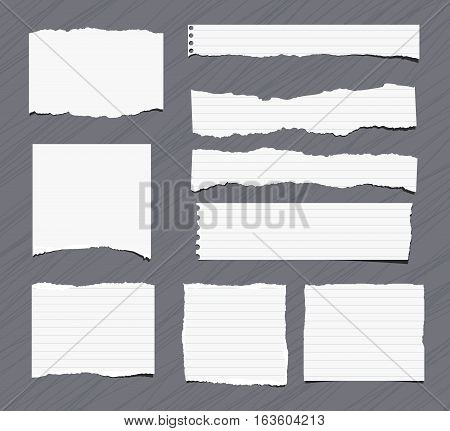 Pieces of white torn note, notebook, copy book paper sheets stuck on grey background.