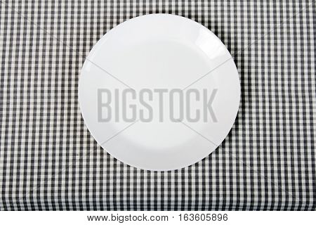 white plate on checkered table cloth - kitchen background