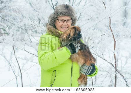 Woman embracing cute dog Pekingese in winter park