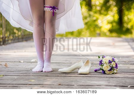 The young bride in a white dress standing on a wooden bridge barefoot. Shoes girl and a bouquet lying there. Bride standing barefoot on the bridge.