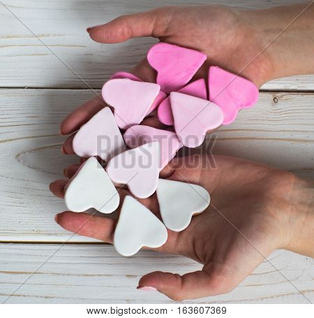 Pink cookies in woman hands heart shape white background