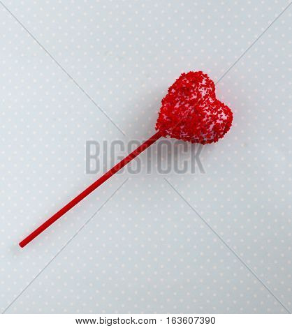 Red cakepop heart shape blue background, sweet